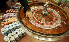 """A staff member demonstrates the roulette wheel for the media at the new casino """"Grand Lisboa Casino"""" in Macau, Sunday, Feb. 11, 2007. Billionaire gambling king Stanley Ho celebrated the long-awaited opening Sunday of his Grand Lisboa casino _ a gleaming gold complex that is Ho"""
